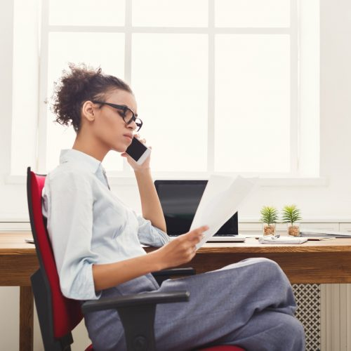 Young serious african-american businesswoman talking by phone with papers, sitting at modern office workplace, side view. Business consulting, copy space