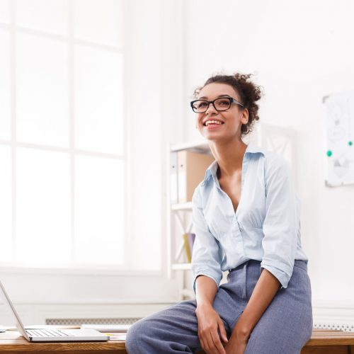 Businesswoman in modern office. Happy smiling woman working on laptop at office, copy space