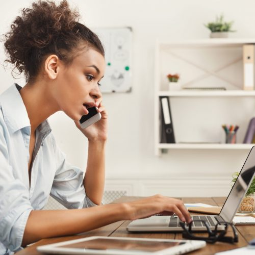 Concentrated african-american business woman at work talking on phone, sitting at her working place in office, copy space