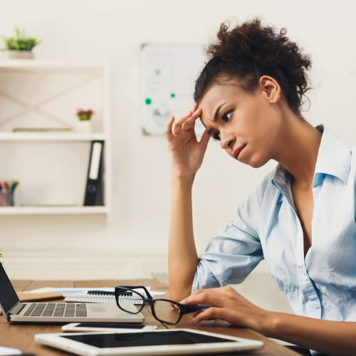 Deadline stress concept - sad african-american business woman sitting at desktop in office, working on laptop and holding hand on head. Hard working day, copy space
